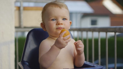 HD1080p25 Blond Baby (10 months old) eating a peach. Happy.