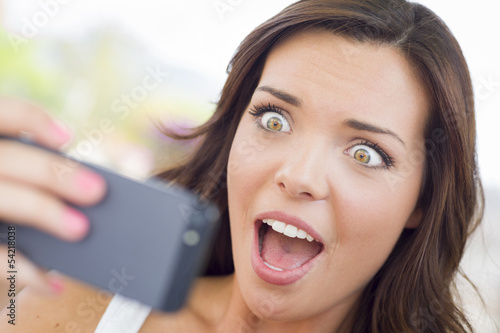 Shocked Young Adult Female Reading Cell Phone Outdoors