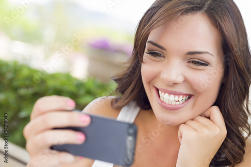 Pretty Adult Female Texting on Cell Phone Outdoors