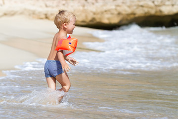 Three year old boy playing on the beach