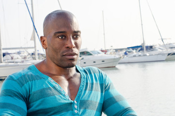 Handsome black man in a summer marine scene with yachts