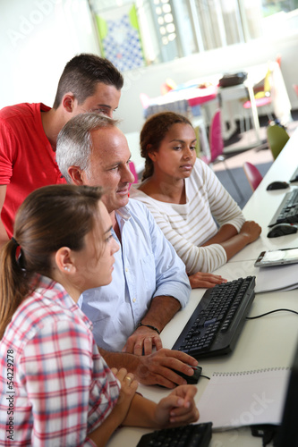 Teenagers with teacher in computers' class