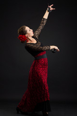 Spanish woman dancing flamenco on black