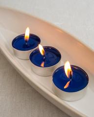 Drei Teelichter mit blauem Wachs in einer Keramikschale