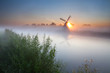 summer sunrise over river and windmill