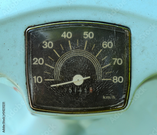 A Grungy Speedometer On A Sky Blue Scooter