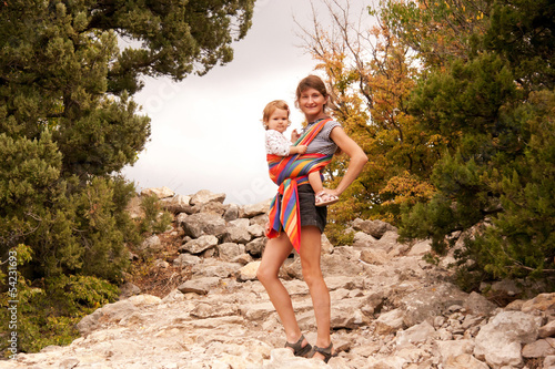 Mother and baby in sling in  mountains