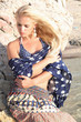 beautiful blond woman.stone blue polka dot scarf.rock by sea