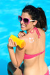 Funny woman applying sunscreen on summer