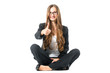 Young woman showing success sitting cross legged
