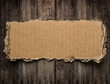 Torn cardboard on wood background