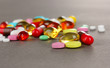 Assortment of pills, tablets and capsules on grey background