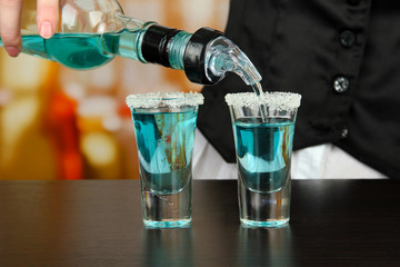 Barmen hand with bottle  pouring beverage into glasses,