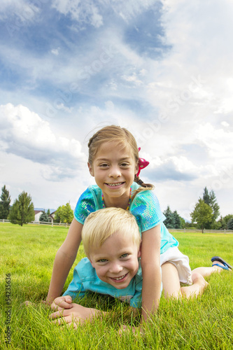 Happy kids playing in the grass on summer day