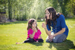 Mother Blowing Dandelions with daughter