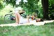 Frau mit Blumenstrauß auf Picknickdecke