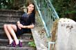 junges Model sitzt auf alter Treppe