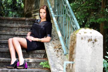 hübsche Frau sitzt auf alter Treppe