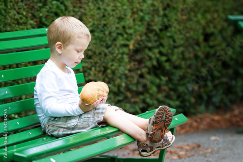Three years old boy eating bread