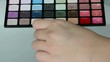 Woman is testing eye shadow palette with her backhand