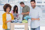 Team of volunteers taking out clothes from a donation box