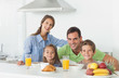Portrait of cute family having breakfast