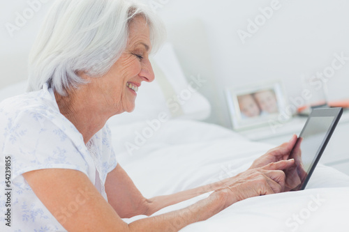 Woman using a tablet while she is lying on bed