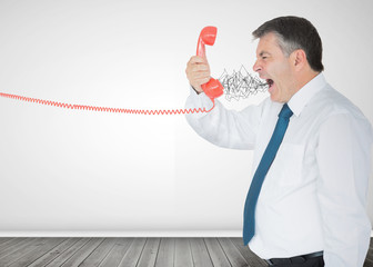Mature businessman screaming on the phone