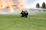 Strażacy gaszą poża budynków.