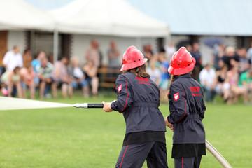 Strażacy dziewczyny, leją wodę z węża strażackiego.