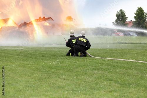 Strażacy gaszą poża budynków. - 54241230