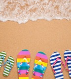 Family's flip flop pairs on sea surf with copy space for your te
