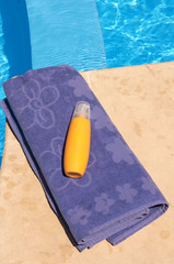 Blue towel and sunscreen lotion near the pool