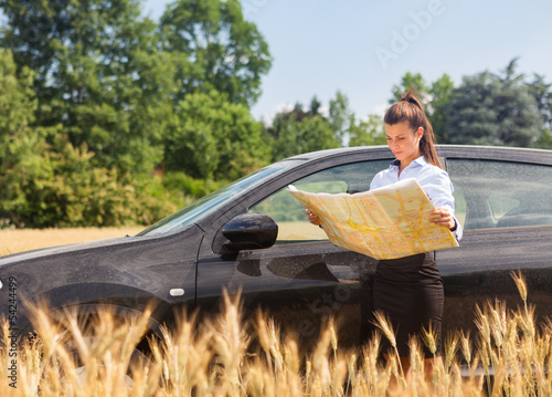 Woman lost with car in a corn field and looking at the map