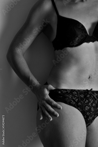Woman in black underwear stand against wall artistic conversion