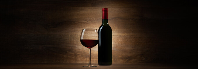 green bottle with red wine and glass on a wood panorama
