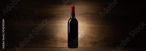 green bottle with red wine on a wood panorama background