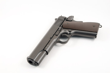 Loaded hand gun against white background of the 1911 variety