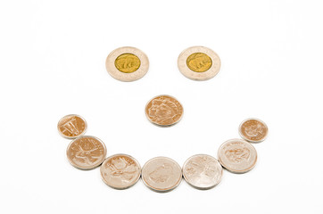 Coins arranged into a happy smiling face using Canadian money
