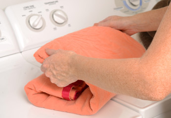 laundry and folding orange towel