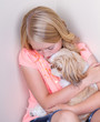 teen hugging dog in corner