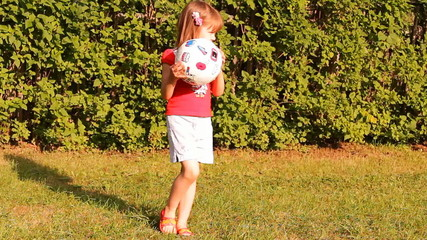 девочка играет в мяч на природе