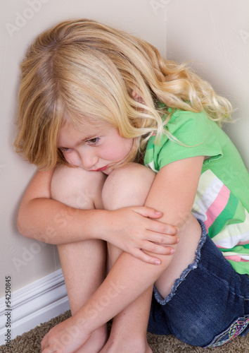 child sitting in corner