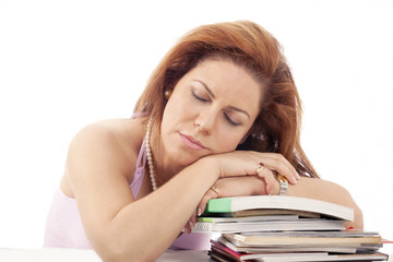 Tired woman asleep on books