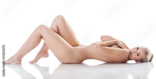 Leinwanddruck Bild Amazing naked blonde smiling lying in studio