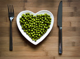 Heart-shaped plate with green peas on wood