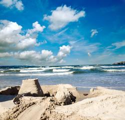 Kinderspiel: Sandburg am Meer mit blauem Himmel und Wolken