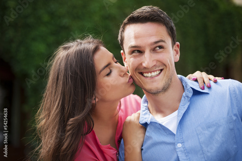 Young woman kissing her boyfriend on the cheek