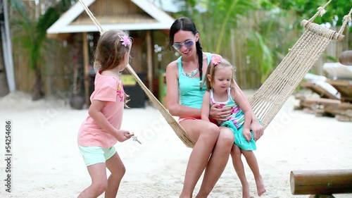 Fashion mother and her daughters relaxing in hammock in exotic
