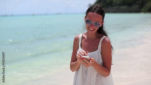 young beautiful woman on the beach looking on her phone